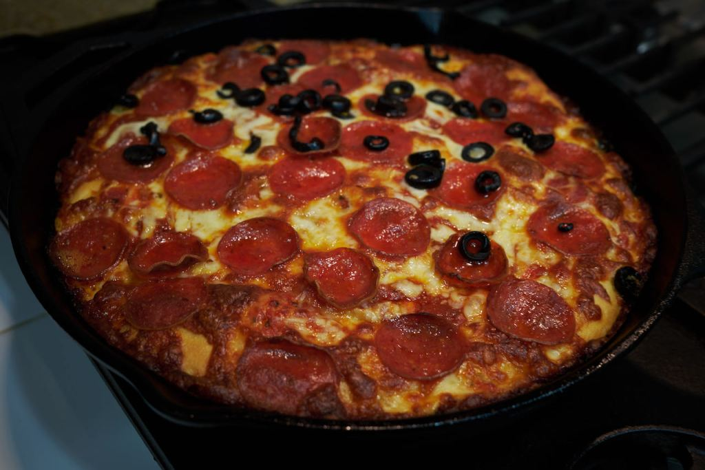 a color picture of a cooked pepperoni pan pizza, half of it with sliced olives, made from a King Arthur Baking Company recipe