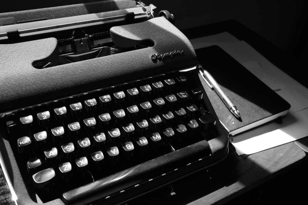 a black and white photo of a Olympia SM2 typewriter, some paper, a notebook, and a pen on a typewriter desk. There is some sunlight on the typewriter, coming from a window that isn't in frame.