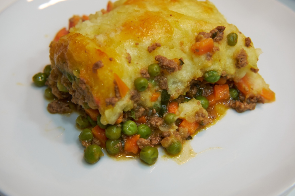 A picture of a square of cottage pie on a white plate. There are peas and carrots along with the ground beef, with a little spilling out on the plate. The mashed potato topping is nicely browned.