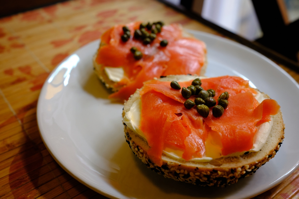 a picture of an everything bagel topped with smoked salmon, cream cheese, and capers.