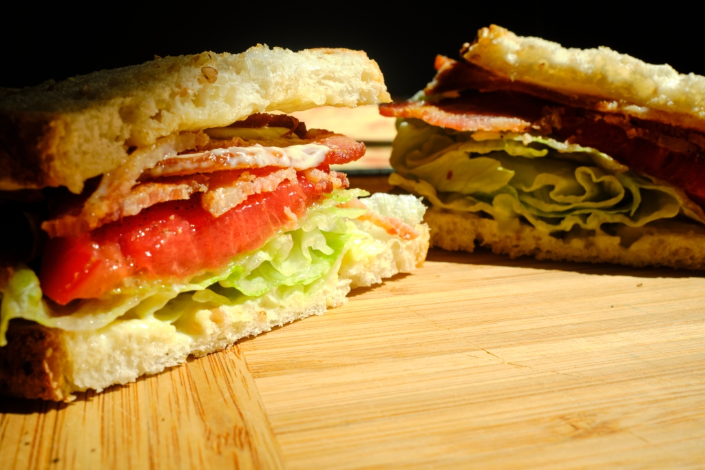 A picture of the cross section of a BLT sandwich, made using homegrown tomatoes and Kewpie mayo, as well as applewood speed bacon and iceberg lettuce on sourdough bread.