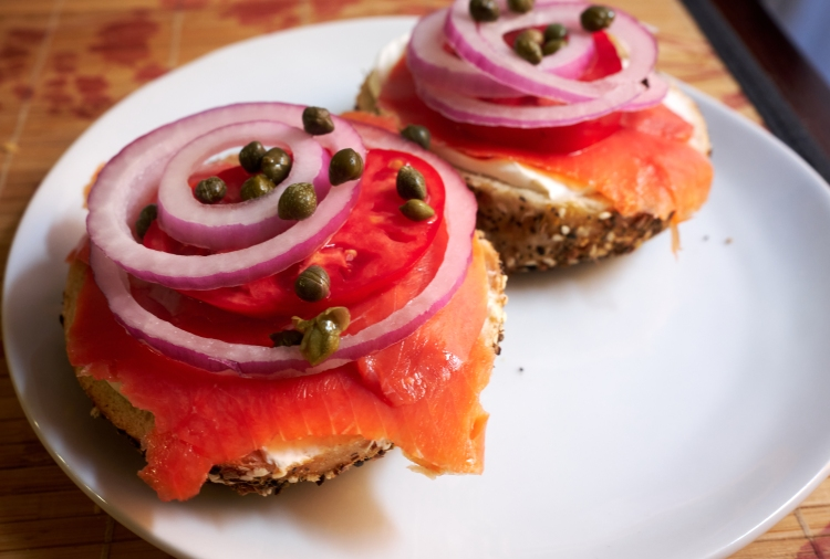 a photo of red onion, tomato, capers, cream cheese, and smoked salmon layered on top of an everything bagel