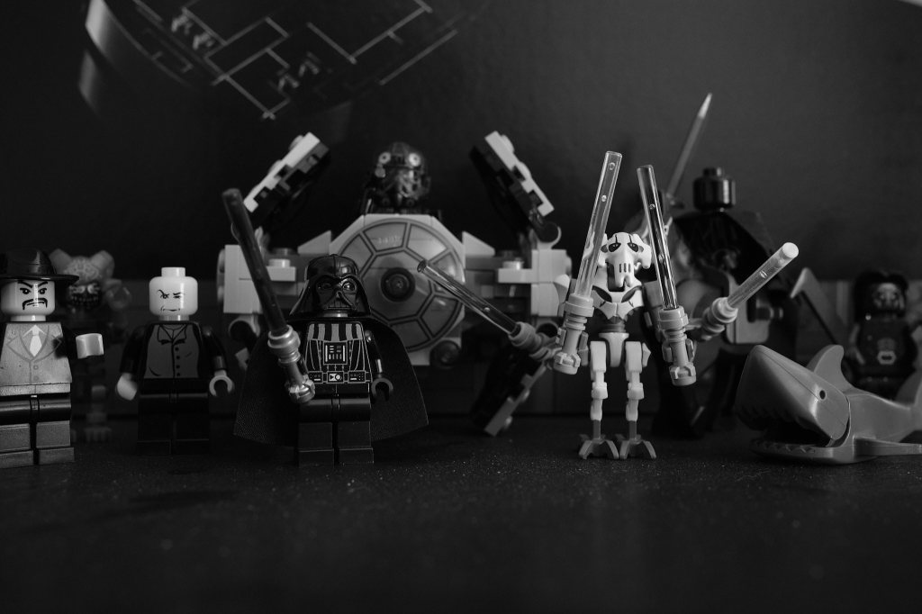 a black and white picture of Lego mini figures. They include Darth Vader, General Grievous, a Nazgul, a shark, Voldemort, and others that are blurred in the background.
