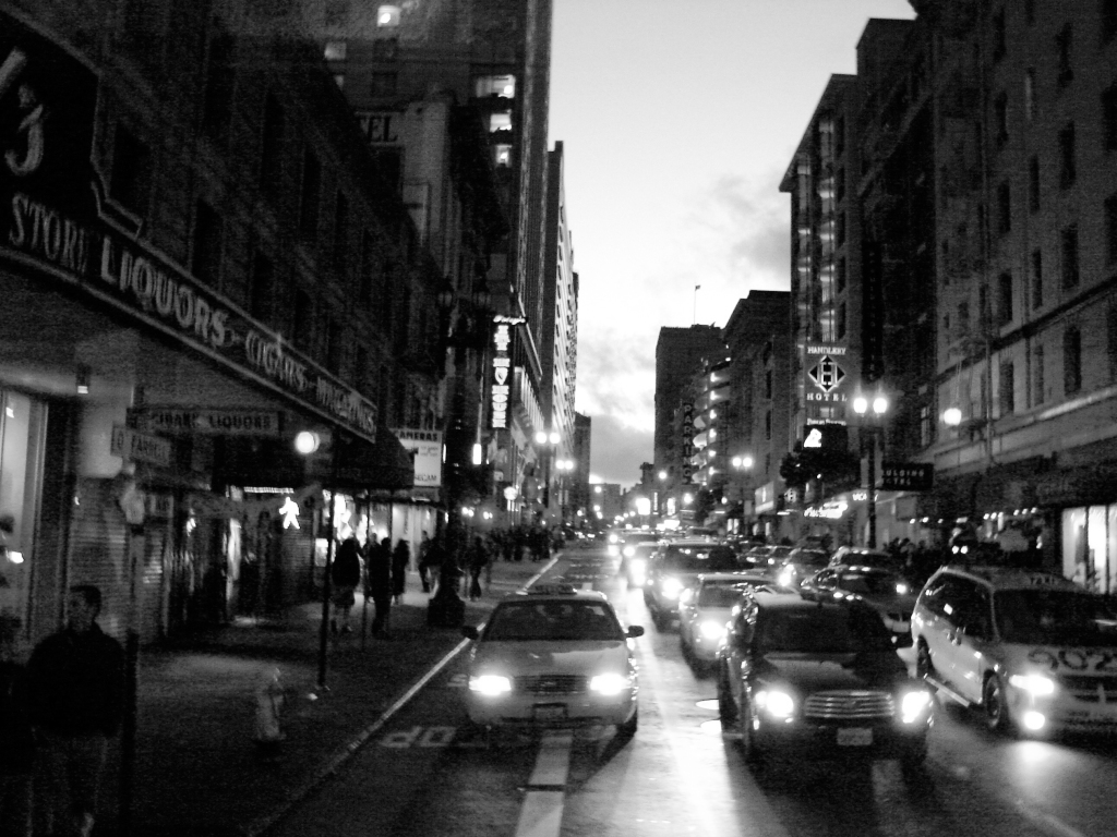 a black and white picture of a busy street in San Francisco. There are three lanes of cars stopped, and facing forward. The sidewalk, to the far left of the frame, has pedestrians moving to and from.