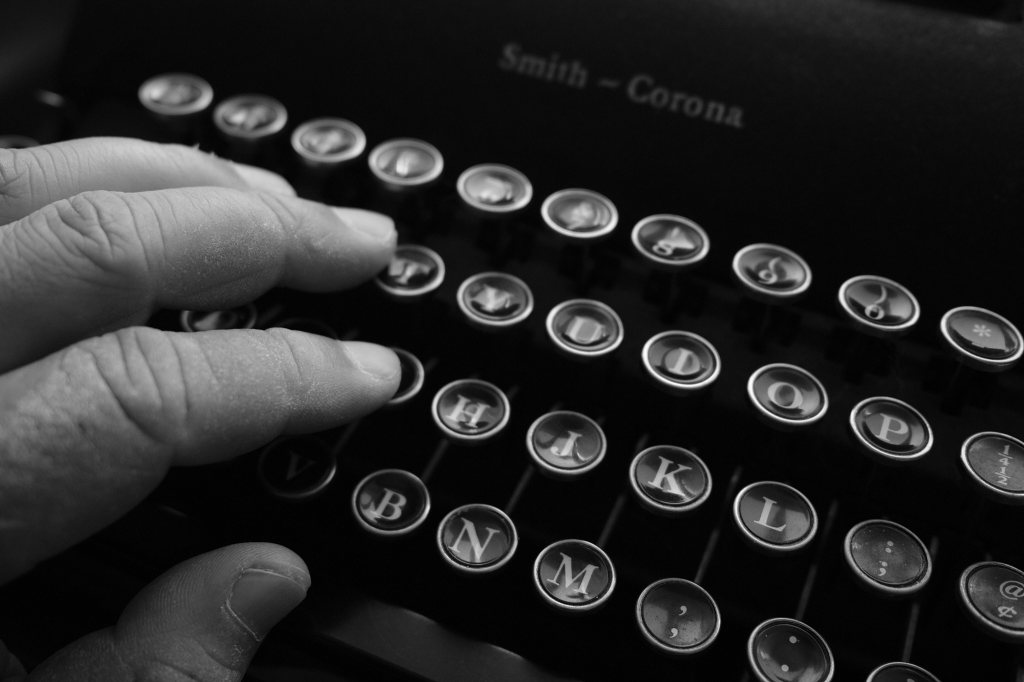 a black and white picture of fingers resting on a typewriter's keys.