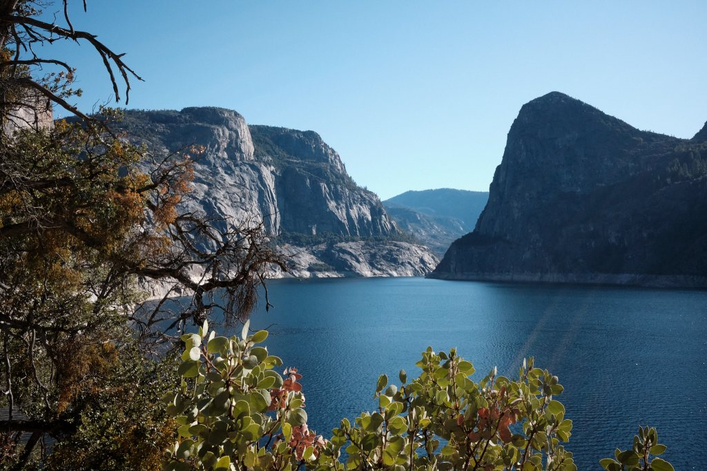 a picture of a valley at Hetch Hetchy, part of Yosemite National Park. In the foreground are some plants. In the middle is clear smooth water, part of the reservoir, and the background has high granite mountains.